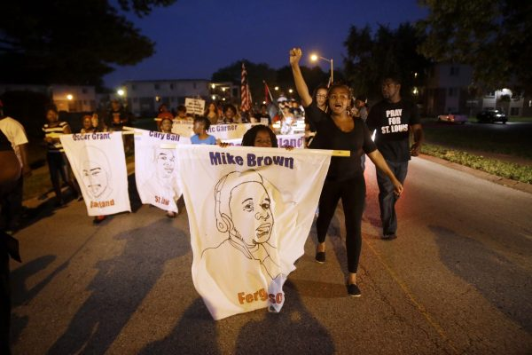 Protesters march down Canfield Drive near where Michael Brown was killed in Ferguson, Mo., on Aug. 7, 2015. Sunday will mark one year since Brown was fatally by Ferguson police officer Darren Wilson. (AP Photo/Jeff Roberson)