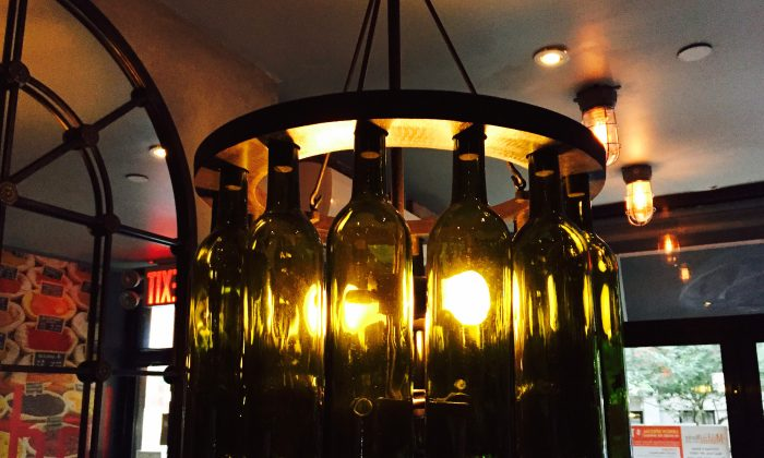 This July 25, 2015 photo shows a light fixture at Malai Marke, a stylish Indian restaurant in New York City's East Village, where light in the dining room glows from bulbs surrounded by green wine bottles arranged in a circle, empty but corked. (AP Photo/Beth J. Harpaz)