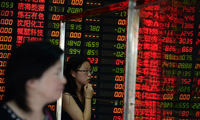 Investors check a screen displaying share prices at a security firm in Shanghai on July 6, 2015.     (STR/AFP/Getty Images)