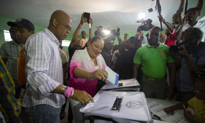 Haiti's first lady Sofia Martelly, center, casts her ballot next to President Michel Martelly, left, during parliamentary elections in Port-au-Prince, Haiti, Sunday, Aug. 9, 2015. (AP Photo/Dieu Nalio Chery)
