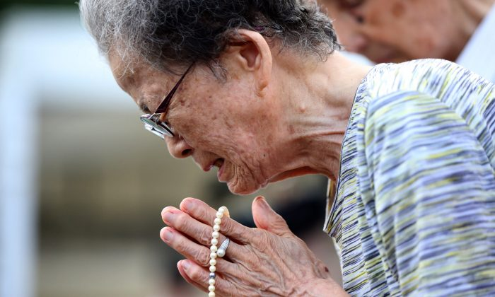 A woman cries as she offers prayers at the Peace Park before the 70th anniversary of the Nagasaki atomic bombing in Nagasaki, southern Japan Aug. 9, 2015. (AP Photo/Eugene Hoshiko)