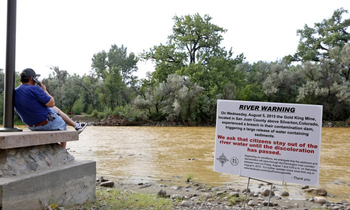 A warning sign from the city is displayed in front of the Animas River as orange sludge from a mine spill upstream flows past Berg Park in Farmington, N.M., Aug. 8, 2015. (Alexa Rogals/The Daily Times via AP)