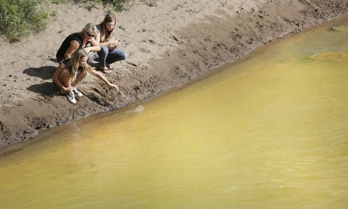 Kim Cofman and her daughters Acacia, 12, left, and Cayenne, 14, try to stir up sludge from the Gold King Mine that covers the bottom the Animas River on Saturday, Aug. 8, 2015, in Durango, Colo., near the 32nd Street Bridge but find the only way to disturb it is to dig into the yellow muck. Toxic waste is still flowing from the Gold King Mine. (Jerry McBride/The Durango Herald via AP)