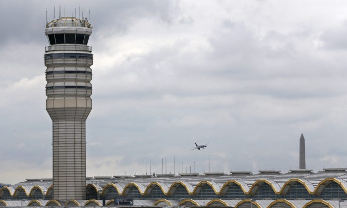 An airplane flies between the air traffic control tower and the Washington Monument at Washington's Ronald Reagan National Airport on Monday, Aug. 10, 2015. (AP Photo/Jacquelyn Martin)