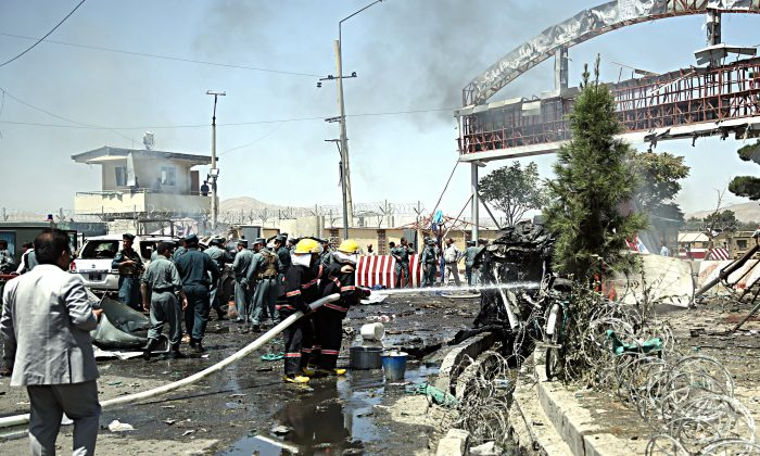 Afghan fire fighters extinguish vehicles on fire after an attack at the main gate of International Hamed Karzai Airport in Kabul, Afghanistan, Monday, Aug. 10, 2015. (AP Photo/Massoud Hossaini)