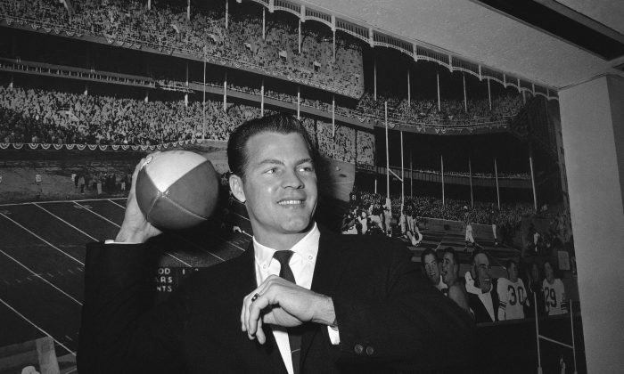 Halfback Frank Gifford cocks his passing arm as he stands in front of photo mural of the Polo Grounds at the offices of the New York Giants in New York's Coliseum, on April 2, 1962. (AP Photo)