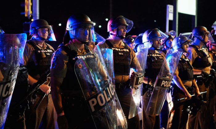 St. Louis County Police and Missouri State Highway Patrol troopers stand guard as protesters march on West Florissant Avenue in Ferguson, Missouri on August 9, 2015. A day of peaceful remembrance marking the anniversary of 18-year-old teen Michael Brown's killing by police in the US city of Ferguson came to a violent end on August 9 as gunfire left at least one protester injured. (Michael B. Thomas/AFP/Getty Images)