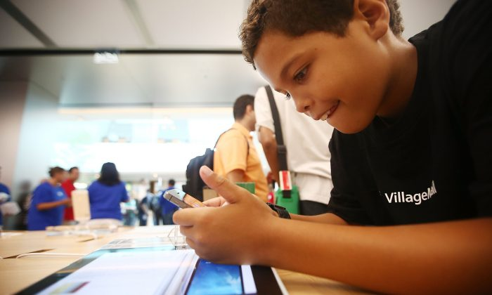 A boy plays with an iPhone in Brazil's first Apple retail store minutes after it opened to the public for the first time in the Village Mall shopping center on February 15, 2014 in Rio de Janeiro, Brazil. (Photo by Mario Tama/Getty Images)