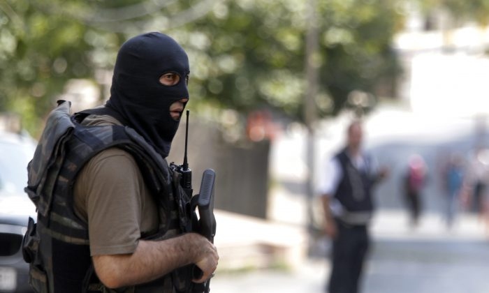 A masked Turkish police officer secures a road leading to the U. S. Consulate building in Istanbul, Monday, Aug. 10, 2015. (AP Photo/Lefteris Pitarakis)