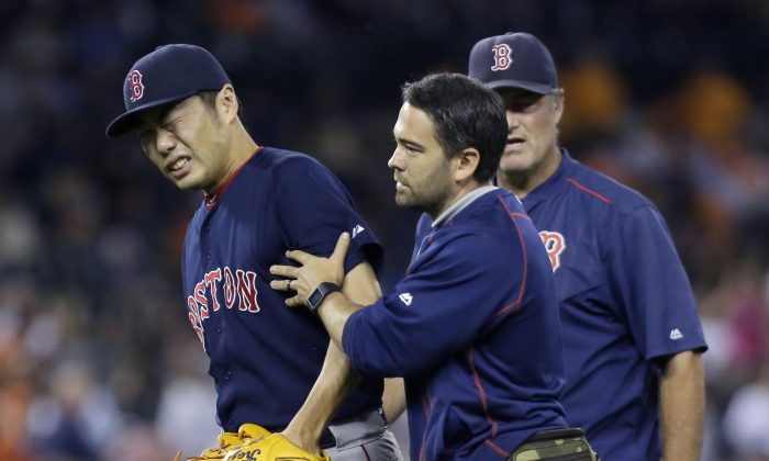 Koji Uehara #19 of the Boston Red Sox is led off the field by trainer Brad Pearson, with manager John Farrell following, after taking a line drive off the right wrist from Ian Kinsler of the Detroit Tigers during the ninth inning at Comerica Park on August 7, 2015 in Detroit, Michigan.(Duane Burleson/Getty Images)