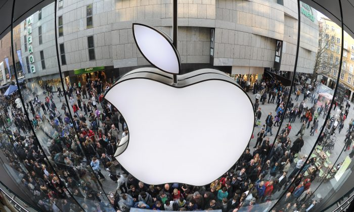 A giant Apple logo can be seen as customers wait for the new Apple iPad 2 in front of the Apple-store in the southern German city of Munich on March 25, 2011. (Christof Stache/AFP/Getty Images)