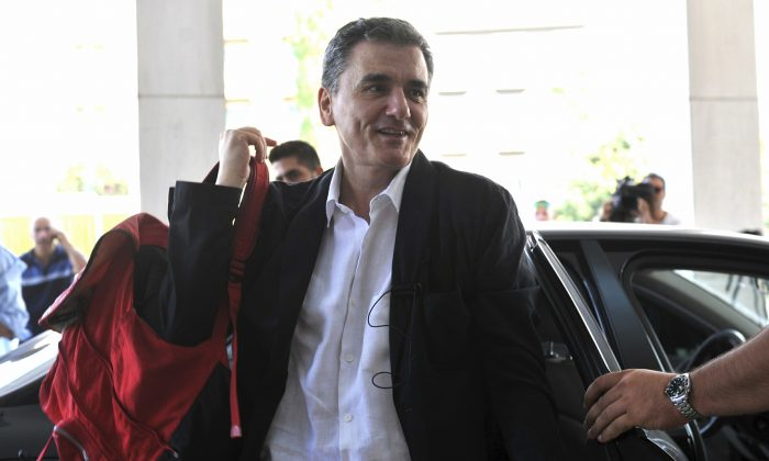 Greek Finance Minister Euclid Tsakalotos arrives for a meeting with senior negotiators at a hotel in Athens on July 31, 2015. Greece has essentially concluded its bailout talks with its creditors, with just a few details remaining for the deal to be formally clinched, Greek officials said Tuesday, Aug. 11. (Giannis Kotsiaris/InTime News via AP)
