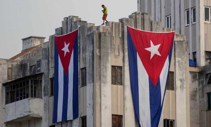 A man walks along the ledge of a building after hanging two giant Cuban flags, next to the US embassy, in Havana, Cuba, on Aug. 11, 2015. (Ramon Espinosa/AP Photo)
