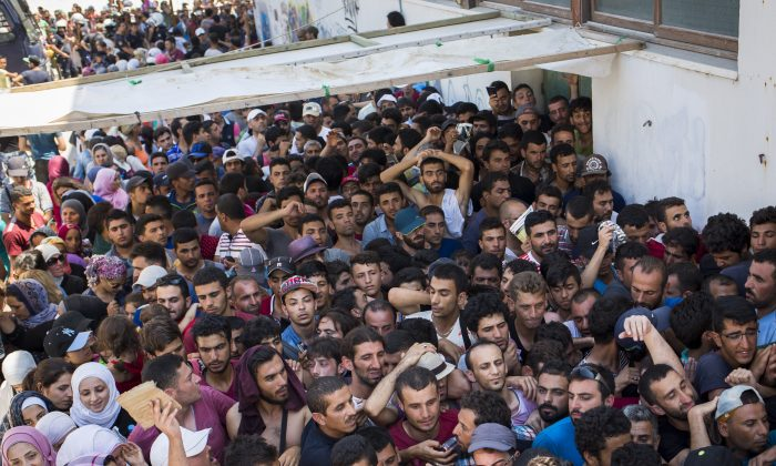 Syrian migrants and refugees gather at a makeshift migrant detention center at an abandoned football stadium on Kos Island, Greece, on Aug. 12, 2015. (Alexander Zemlianichenko/AP)