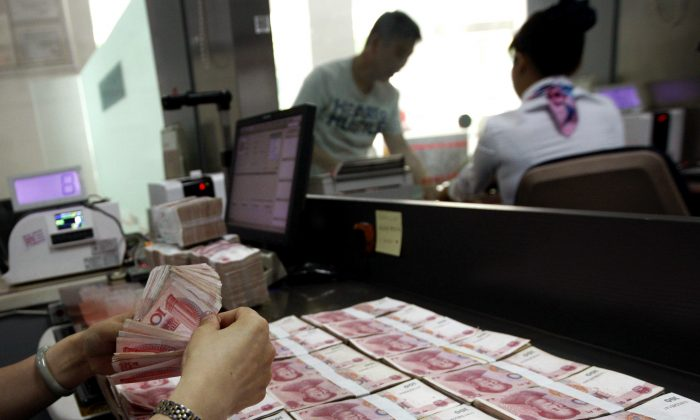 A bank clerk counts Chinese notes in Huaibei, Anhui province, Aug. 11, 2015. (Chinatopix via AP)