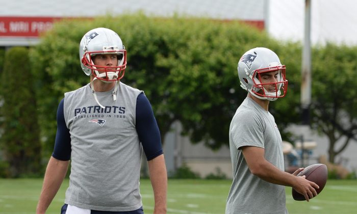 Tom Brady #12 of the New England Patriots, (L) and backup quarterback Jimmy Garappolo #10 work out during organized team activities at Gillette Stadium on June 4, 2015 in Foxborough, Massachusetts. (Darren McCollester/Getty Images)