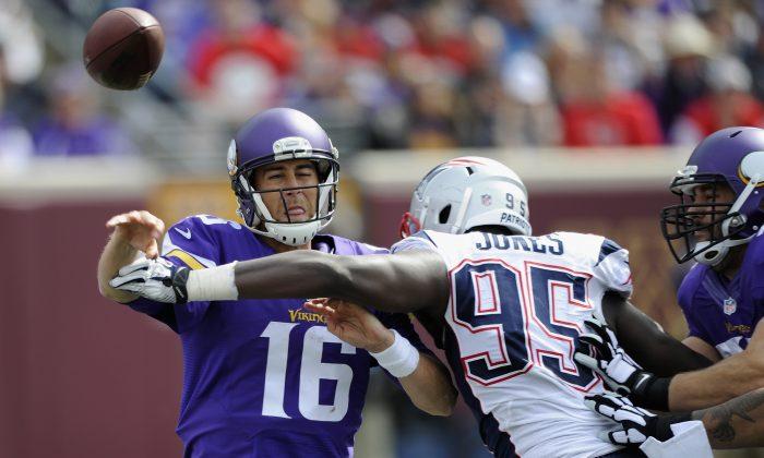 Matt Cassel #16 of the Minnesota Vikings passes under pressure from Chandler Jones #95 of the New England Patriots, September 14, 2014. (Hannah Foslien/Getty Images)