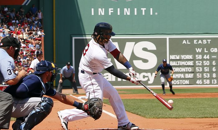 Boston Red Sox's Hanley Ramirez connects on an RBI sacrifice fly out during the first inning of a baseball game against the Tampa Bay Rays at Fenway Park in Boston, Saturday, Aug. 1, 2015. (AP Photo/Winslow Townson)