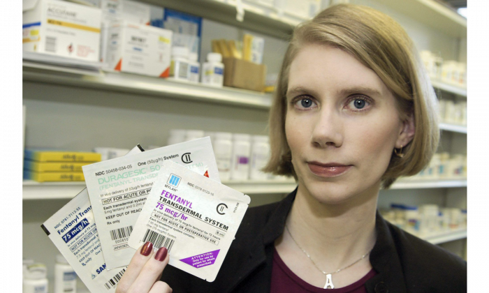Amy Tiemeier, assistant professor of Pharmacy Practice at St. Louis College of Pharmacy in Michigan, holds up three different versions of the pain-relieving fentanyl patch on April 26, 2006. Trafficking in and deaths from the dangerous opoid has increased in Canada. (AP Photo/Tom Gannam)