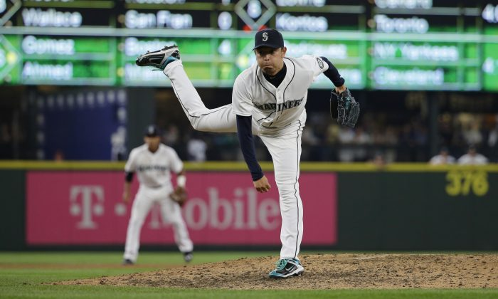 Seattle Mariners starting pitcher Hisashi Iwakuma follows through on a pitch against the Baltimore Orioles in the ninth inning of his no-hitter baseball game, Wednesday, Aug. 12, 2015, in Seattle. The Mariners beat the Orioles 3-0. (AP Photo/Ted S. Warren)