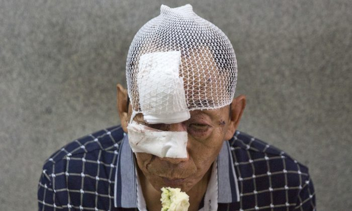 A man with his wounds bandaged eats a bun in a hospital receiving victims of an explosion in northeastern China's Tianjin municipality on Thursday, Aug. 13, 2015. (AP Photo/Ng Han Guan)