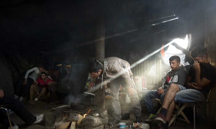 In this Sunday, Aug. 9, 2015 file photo, Afghan migrants stay inside a tent as they cook food at a camp set near Calais, northern France. (AP Photo/Emilio Morenatti)