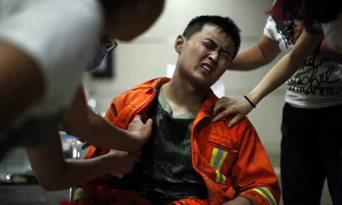 An injured firefighter grimaces as he is examined in a hospital following explosions in northeastern China's Tianjin municipality, Thursday, Aug. 13, 2015. (Chinatopix Via AP)
