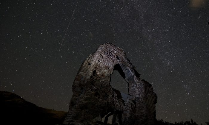 A long exposure image showing an aeroplane passing in the sky during the Perseids meteor shower over the remains of St. Ilia Roman early Christian basilica dated back to the 5th6th century AD near the town of Pirdop, early on August 12, 2015. The Perseid meteor shower occurs every year in August when the Earth passes through the debris and dust of the Swift-Tuttle comet. The Perseid meteor shower -- an annual display of natural fireworks -- should be particularly spectacular this year, with extra-dark skies expected to create optimal stargazing conditions, astronomers said on August 7, 2015. (Nikolay Doychinov/AFP/Getty Images)