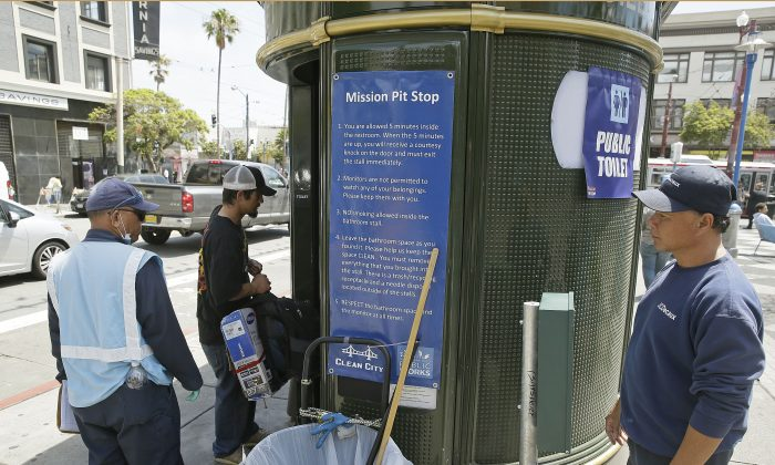 In this Thursday, July 30, 2015, photo an attendant looks on as a man enters a Pit Stop public toilet outside a Mission District transit station in San Francisco. (AP Photo/Eric Risberg)