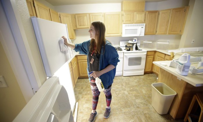 In this Friday, Aug. 7, 2015, student Emilee Gull cleaning a dorm room in Eccles Living Learning Center at Southern Utah University, in Cedar City, Utah. (AP Photo/Rick Bowmer)