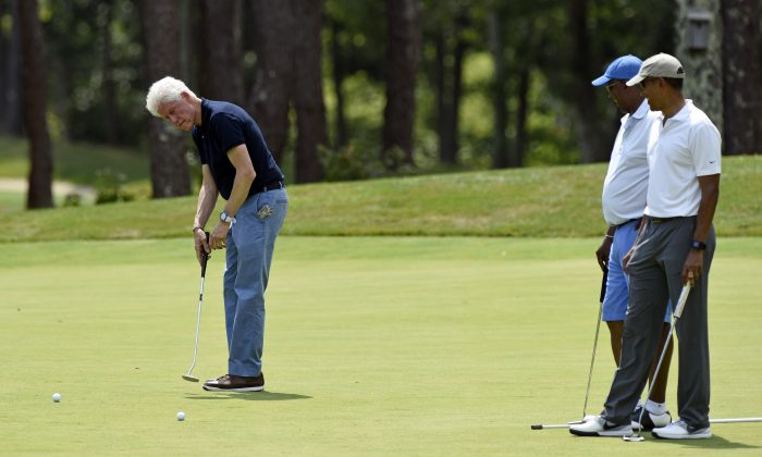 Former US President Barack Obama, right, and Ron Kirk, center, former United States Trade Representative, watch as former US President Bill Clinton putts as they play golf on the first hole at Farm Neck Golf Club in Oak Bluffs, Mass., on Martha's Vineyard on Aug. 15, 2015. (Susan Walsh/AP Photo)