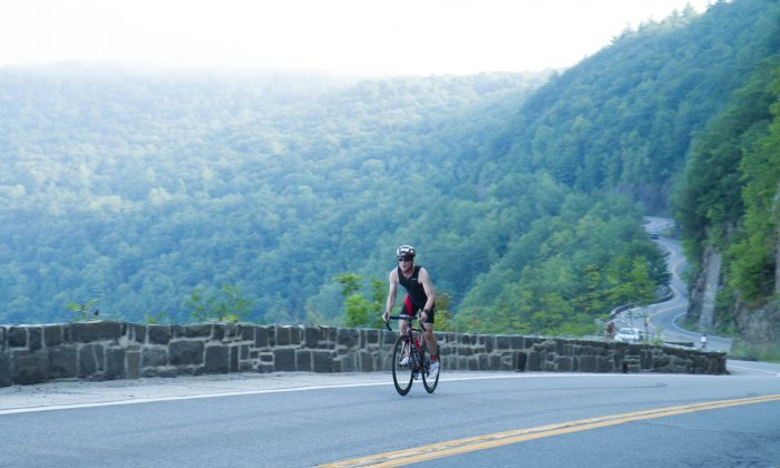 Steven Cercy bikes up a steep hill in the Hawk's Nest portion of Route 97 outside Port Jervis, N.Y. for the inaugural Tri-State Triathlon on Aug. 16, 2015. (Holly Kellum/Epoch Times)