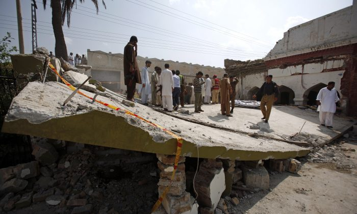 A Pakistani police officer and rescue workers gather at the site of suicide bombing in Shadi Khan, some 80 kilometers (50 miles) northwest from Pakistani capital, Sunday, Aug. 16, 2015. Police in Pakistan say a suicide bombing at the home of a provincial official has killed score of people and more remain trapped in the rubble. (AP Photo/Anjum Naveed)
