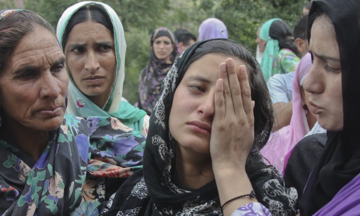 Daughter, center, of Indian civilian Sarpanch Karamat Hussain who was killed in Pakistani shelling wails at Balakot sector in Poonch, Jammu and Kashmir, India, Sunday, Aug.16, 2015. Indian and Pakistani troops traded heavy gunfire and mortar rounds for a seventh day Sunday along the highly militarized line of control dividing the disputed Himalayan region of Kashmir between the two archrivals, officials said. (AP Photo/Channi Anand)