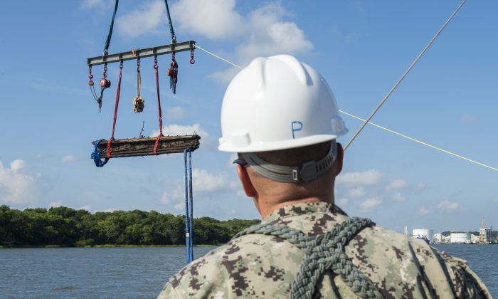 In a Friday, Aug. 14, 2015 photo provided by the US Navy, Chief Warrant Officer 3, Jason Potts, on scene commander for Task Element CSS Georgia, supervises as a piece of casemate, made of railroad ties and timber, which served as the outer layer of armor for CSS Georgia, is raised from the Savannah River in Savannah, Ga.  (MC1 Blake Midnight/US Navy via AP)
