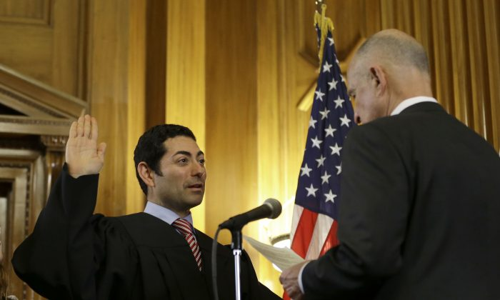 FILE - In this Monday, Jan. 5, 2015 file photo, Mariano-Florentino Cuellar, left, is sworn in as an associate justice to the California Supreme Court by Gov. Jerry Brown during an inauguration ceremony in Sacramento, Calif.  (AP Photo/Rich Pedroncelli, File)