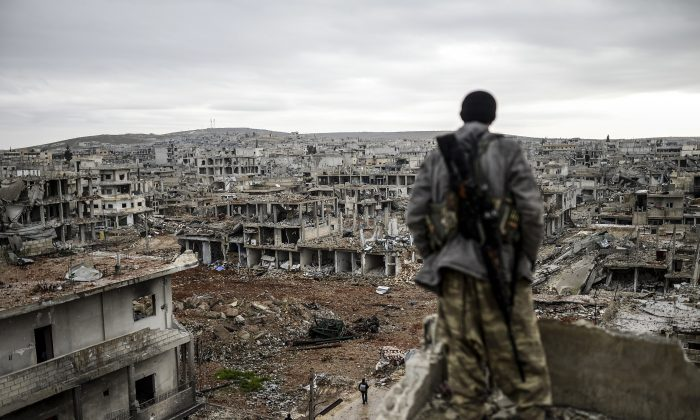 Musa, a 25-year-old Kurdish marksman, looks at the destroyed Syrian town of Kobani, on Jan. 30, 2015. (Bulent Kilic/AFP/Getty Images)