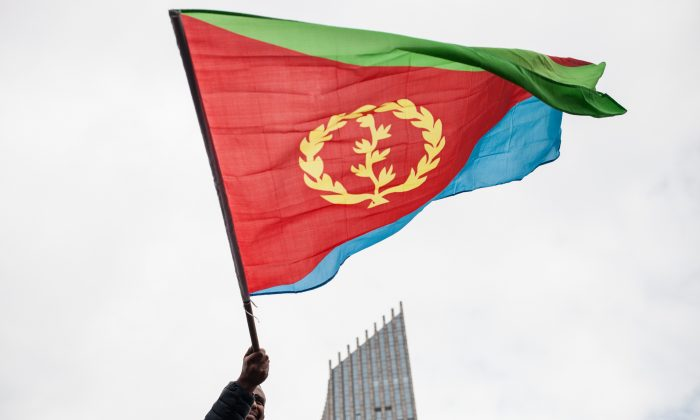 A man waves an Eritrean national flag as hundreds of Eritreans demonstrate in front of the African Union headquarters in support of the U.N. Inquiry report and asking for measures to be taken against Eritrea's human rights violations, in Addis Ababa, on June 26, 2015. (Nichole Sobecki/AFP/Getty Images)