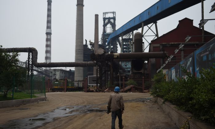 This photo taken on May 28, 2015 shows a demolition worker walking near abandoned buildings at the Shougang Capital Iron and Steel plant in Beijing. Chinese scholar Liu Shijin says that China's economy is at its ebb. (Greg Baker/AFP/Getty Images)