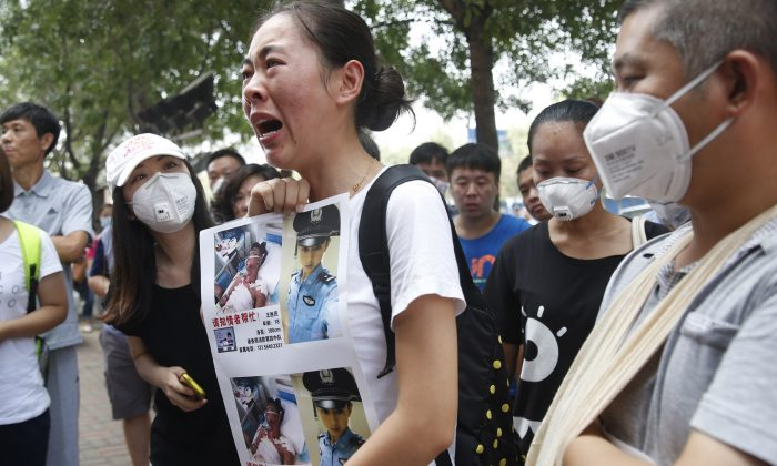 A family member (C) of a missing firefighter from the recent explosions at a chemical warehouse protests outside a hotel where authorities are holding a press conference in Tianjin, China, on August 16. (STR/AFP/Getty Images)