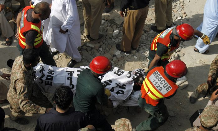 Pakistani rescue workers carry a dead body after recovering it from the rubble at the site of suicide bombing in Shadi Khan, some 80 kilometers (50 miles) northwest from Pakistani capital, Sunday, Aug. 16, 2015. (AP Photo/Anjum Naveed)