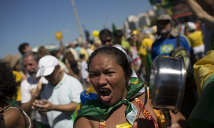 A woman shouts slogans as bangs on a pan during an anti-government protest demanding the impeachment of Brazil's President Dilma Rousseff in Rio de Janeiro, Brazil, Sunday, Aug. 16, 2015.  (AP Photo/Leo Correa)