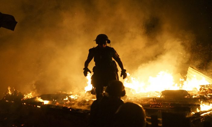 Firefighters extinguish fire at a house destroyed by night-long shelling in Donetsk, eastern Ukraine, on Aug. 16, 2015. (AP Photo/Mstyslav Chernov)