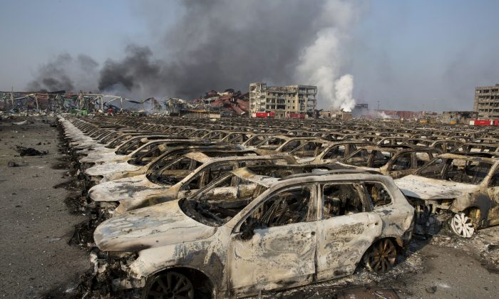 Smoke billows from the site of an explosion that reduced a parking lot filled with new cars to charred remains at a warehouse in northeastern China's Tianjin municipality, Thursday, Aug. 13, 2015. (AP Photo/Ng Han Guan)