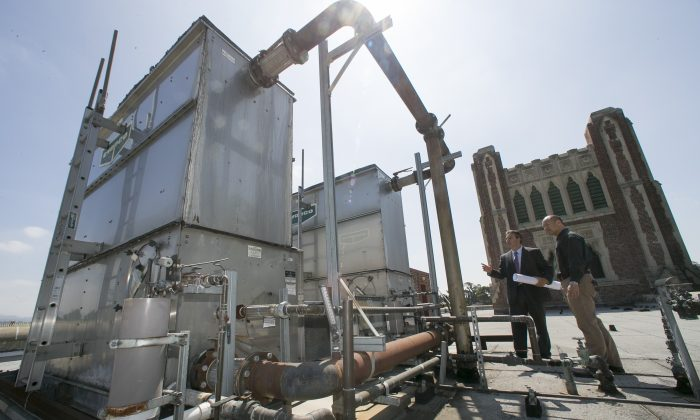 In this Friday, Aug. 7, 2015 photo, Christos Chrysiliou, left, director of architectural and engineering, Los Angeles Unified School District, LAUSD, and Peter Yee, senior project manager, examine an outdated central air conditioner unit at the John Marshall High School in Los Angeles. (AP Photo/Damian Dovarganes)