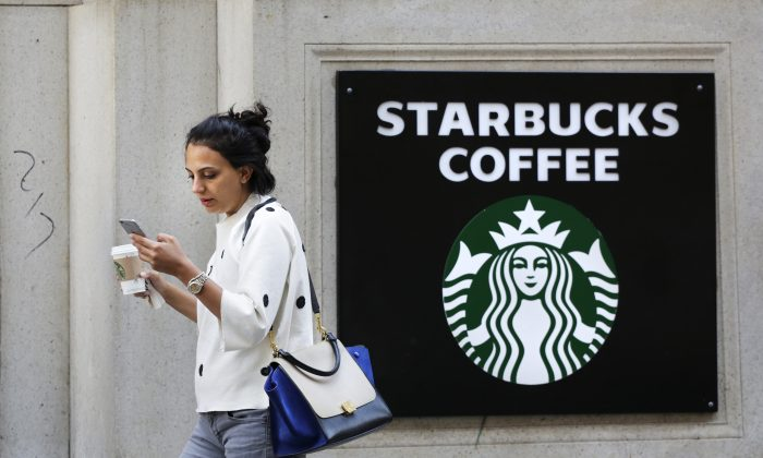 In this July 16, 2015, file photo, a woman walks out of a Starbucks Coffee with a beverage in hand in New York. (AP Photo/Mark Lennihan)