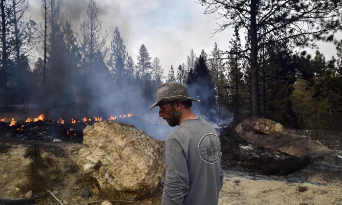 Lorne Brunson stands near the remains of his home, which was lost to a wildfire on Saturday near Coyote Canyon, Sunday, Aug 16, 2015, in Fruitland, Wash. Department of Natural Resources spokeswoman Janet Pierce says most of the state is under a red-flag warning as windy and hot conditions made areas tinder-dry. (Tyler Tjomsland/The Spokesman-Review via AP)