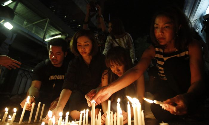 Thai people light candles near the Erawan Shrine at Rajprasong intersection for the victims the day after an explosion in Bangkok, Thailand, Tuesday, Aug. 18, 2015. (AP Photo/Sakchai Lalit)