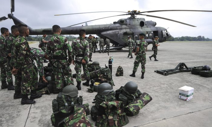 In this photo released by China's Xinhua News Agency, soldiers prepare to leave for the crash site of an Indonesian passenger plane for rescue operations at an air base in Jayapura, Indonesia Tuesday, Aug. 18, 2015. (Veri Sanovri/Xinhua via AP)