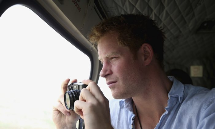 Prince Harry takes a photograph out of the window of a helicopter as he travels over the Muluti Mountains on his way to visit a herd boy night school constructed by his Sentebale charity, in Mokhotlong, Lesotho, on Dec 8, 2014. (Chris Jackson/AP)